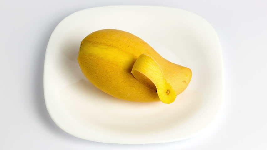 Mango fruit being peeled by itself and served on a plate on white background stop motion animation in 1080p