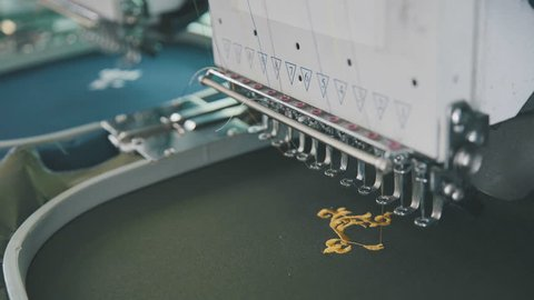 Embroidery machine on T-shirt in Textile Industry at Garment Manufacturers. Machine embroidery is embroidery process whereby sewing machine or embroidery machine is used to create patterns on textiles