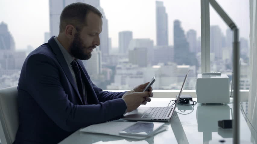 Young businessman sitting with smartphone by desk in the office, 4K  | Shutterstock HD Video #25584728