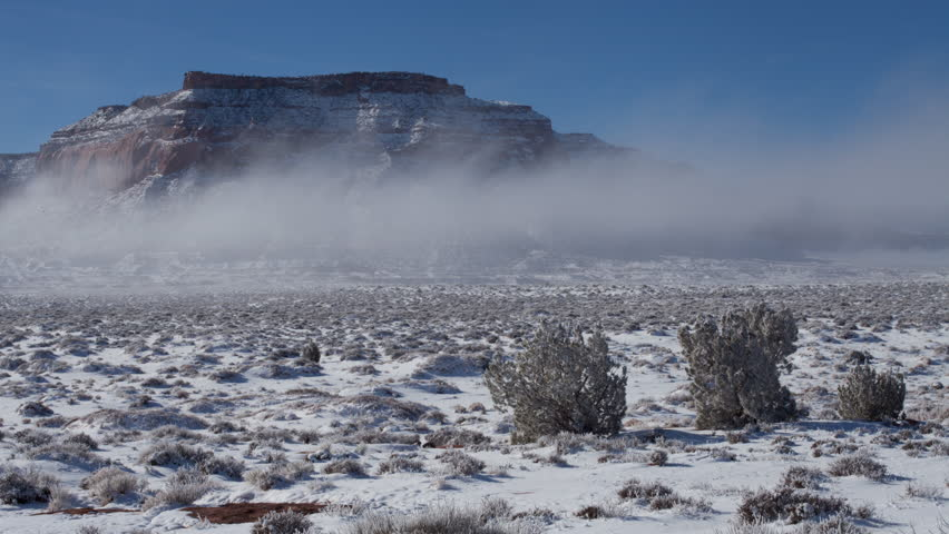 4K time lapse of low fog, blue sky and sunlight on snow covered desert and mesa rock formations in Monument Valley in the Navajo Nation American Indian Reservation in Arizona after a winter snow storm