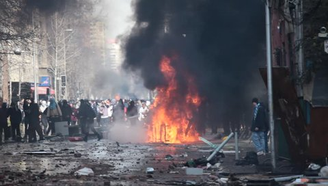 SANTIAGO, CHILE - AUGUST 9: Car overturned and burned and street damage caused during a student strike on August 9, 2011 in Santiago, Chile.