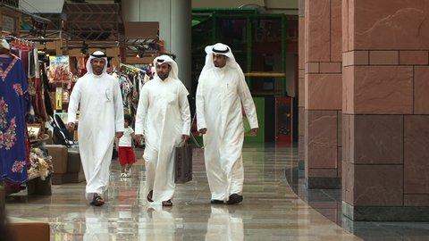 DUBAI, UAE - CIRCA 2008: View of three Emirati men walking together in the souq at Dubai Festival City Mall.