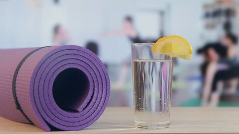 Yoga training, pilates, fitness mat, glass with water and lemon