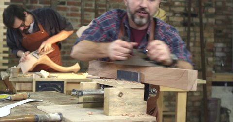 Cabinet-maker is preparing a detail for the table made of beech. In the background we see a young joiner polishing a cabriole table leg/Cabinet - Maker's Handwork is Very Appreciated