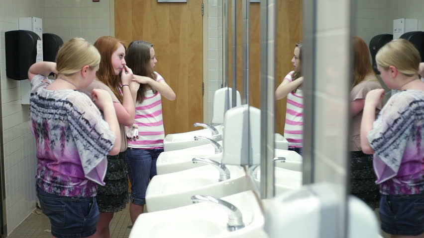 A few girls (students) putting on makeup while talking in a school restroom #2563838