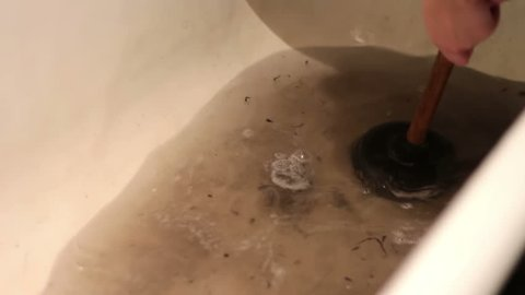 A woman tries to break through the clogged sink in the bathroom using a plunger.Clogged Drain Water in the Bathroom