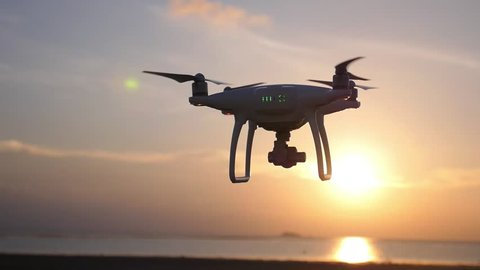 Quadcopter Drone Against Sunset at Beach