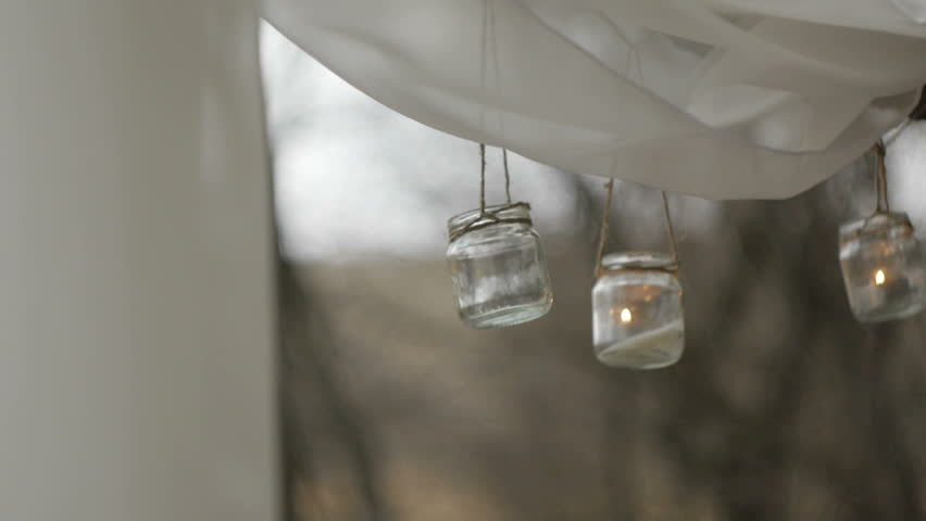 Closeup of the hands ignited the candles with a match in a glass jar suspended on a rope or twine | Shutterstock HD Video #25694108