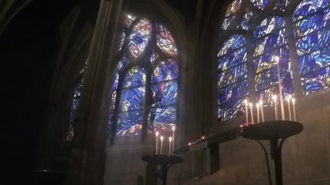 Candles and Blue Stained Glass Massive blue stained glass windows tower over candelabras in a medieval Gothic church.