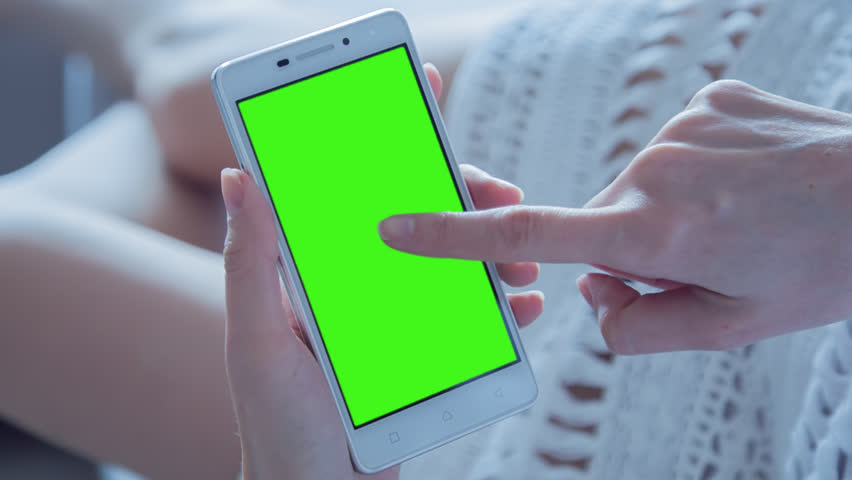 Young Woman laying on a couch uses SmartPhone with pre-keyed green screen. Few types of motion - scrolling up and down, tapping, zoom in and out. Perfect for screen compositing. 10bit ProRes 444 | Shutterstock HD Video #25698044
