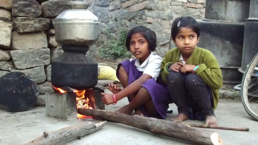 Two girls getting warm front of Hearth in winter season early morning rural village Salunkwadi, Ambajogai, Beed, Maharashtra, India, South East Asia.