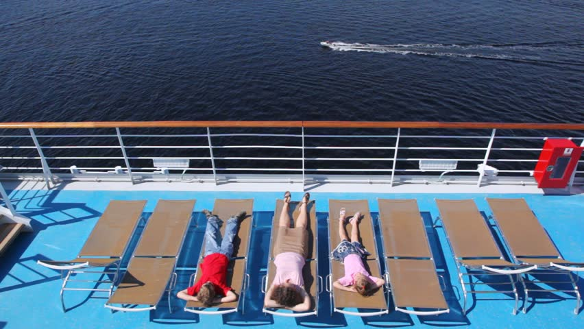 Mother, son with daughter lie in chaise lounge on liner deck