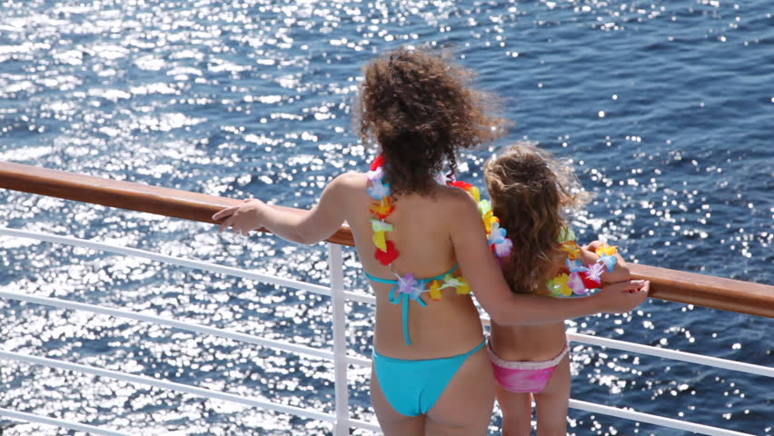 Mother and daughter stand on ship deck in beautiful color garland from flowers in afternoon