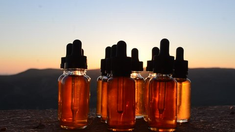 Vape concept. Smoke clouds and vape liquid bottles at sunset time. Useful as background or vape advertisement or vape background