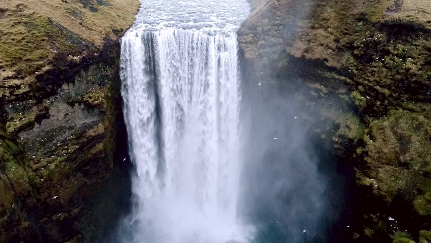 Aerial flight with drone over the famous  Skogar waterfall in Iceland. It is located on the South of the island. Image taken with action drone camera causing distortion and blur. Slow motion shot | Shutterstock HD Video #25716548