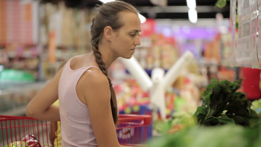 Young attractive mother with little daughter in trolley selecting greens at supermarket, close-up | Shutterstock HD Video #25735328