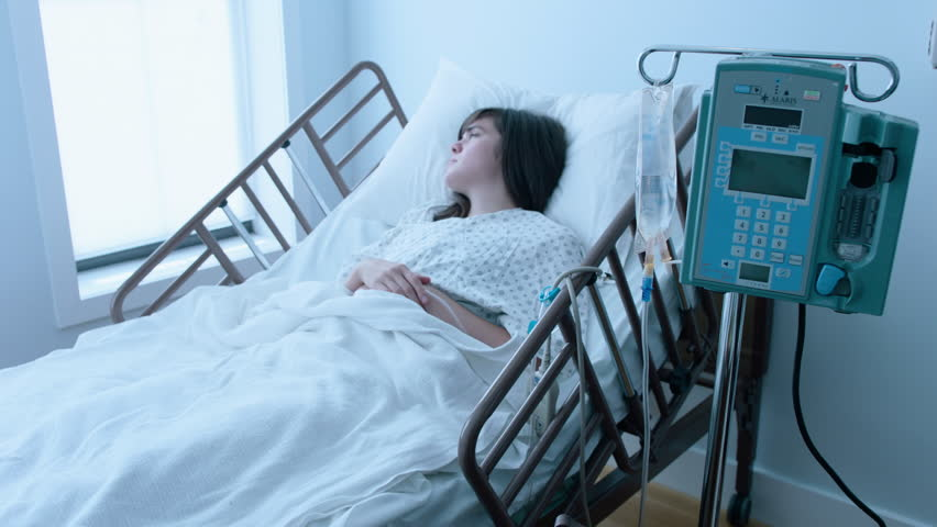 A sick young woman with an IV recovering in a hospital bed next to a window, slow motion, 4K