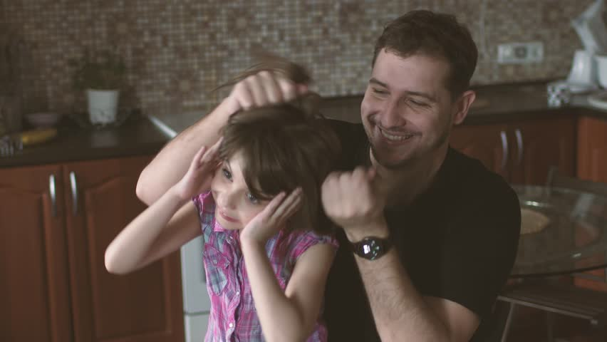 Dad makes funny hairstyles to a little daughter. family is having fun