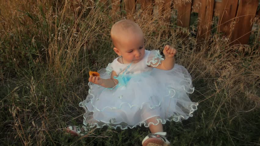 A baby girl sitting in the high grass in a white dress, eating an apricot and looks around. Sunset in summer. | Shutterstock HD Video #25783598