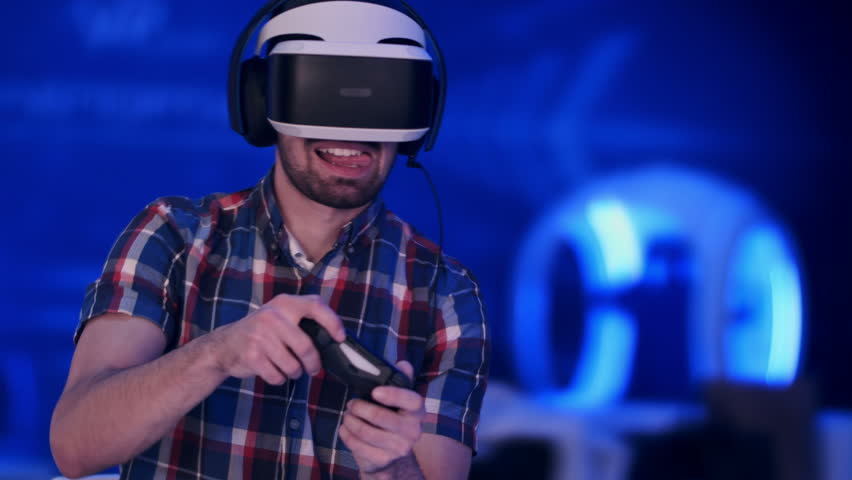 Happy young man with virtual reality headset with controller gamepad playing racing video game | Shutterstock HD Video #25784966