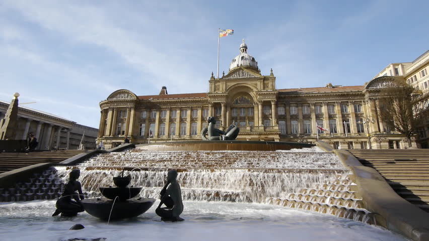 Victoria Square in Birmingham, England. Wide angle shot showing the fountain and statue known as 'the floozy in the jacuzzi'. Quite a few people in the distance. Sunny day.