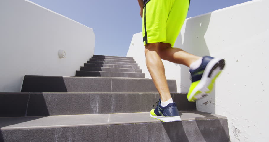 Running on stairs - Runners jogging up stairway. Woman and man runner athletes climbing stairs in workout run outside. Sport, fitness and healthy lifestyle.
