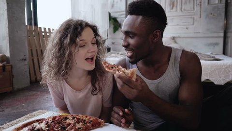 Happy multiethnic couple in pajamas eating fast food. Hungry woman waits the meal, man feeds her a slice of pizza.