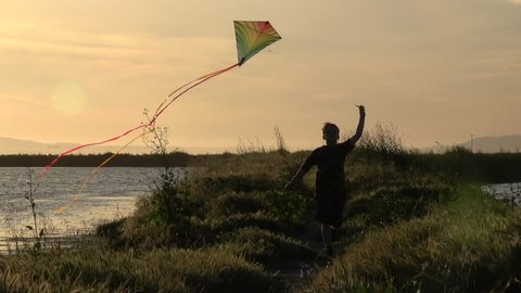 Slow motion silhouette of boy running with kite at sunset
