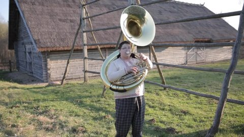 The guy with the tuba makes sharp movements to the right and left down and up.Funny musician movement in plaid pants and a linen shirt . Against the landscape of the village.