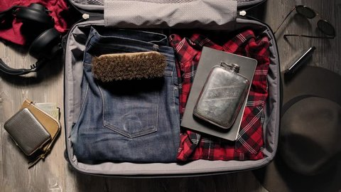 Sequence of hipster items appearing in travel suit case: red plaid flannel shirt, selvedge denim jeans, custom engraved stainless flask, notebook, old leather shoes. Isolated on wooden rustic floor