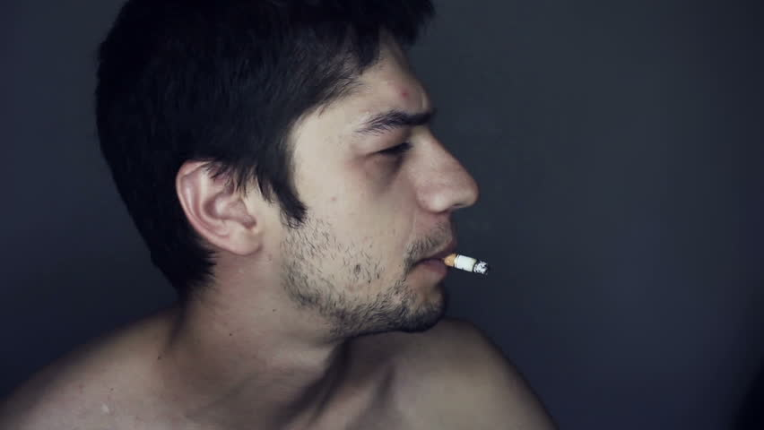 Young bearded man does a trick with a cigarette