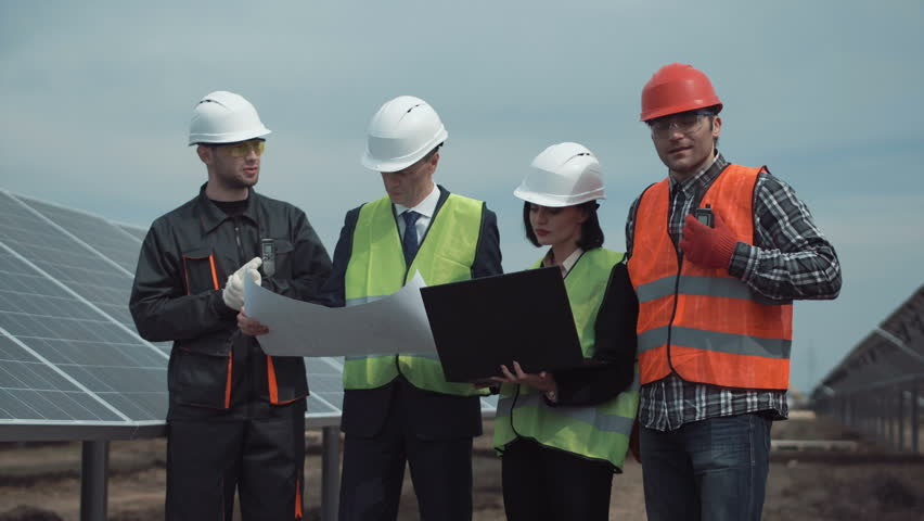 Group of engineers or technicians on a solar farm standing between the photovoltaic panels discussing a blueprint in a management concept of renewable energy and electricity. #25880738