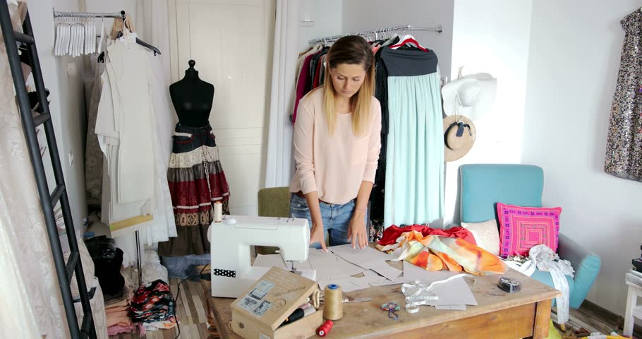 Young female working in parlour and using sewing pattern while making dress.  | Shutterstock HD Video #25895747