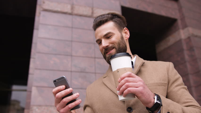 Stylish attractive young man uses the phone and drinking coffee in the street | Shutterstock HD Video #25902578
