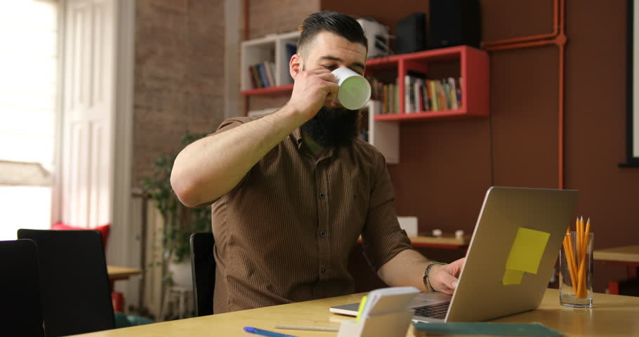 home office multitasking. fine office young serious handsome beard man uses a laptop and drink tea with white cup  in the and home office multitasking