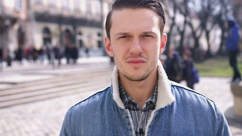 Portrait of attractive serious stylish young man looking into the camera and smiling in the city