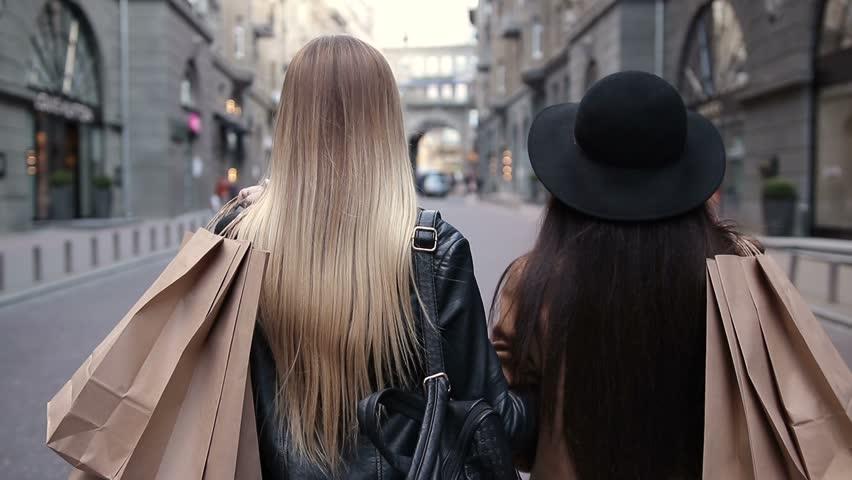 Back view of two walking women with shopping bags | Shutterstock HD Video #25947062