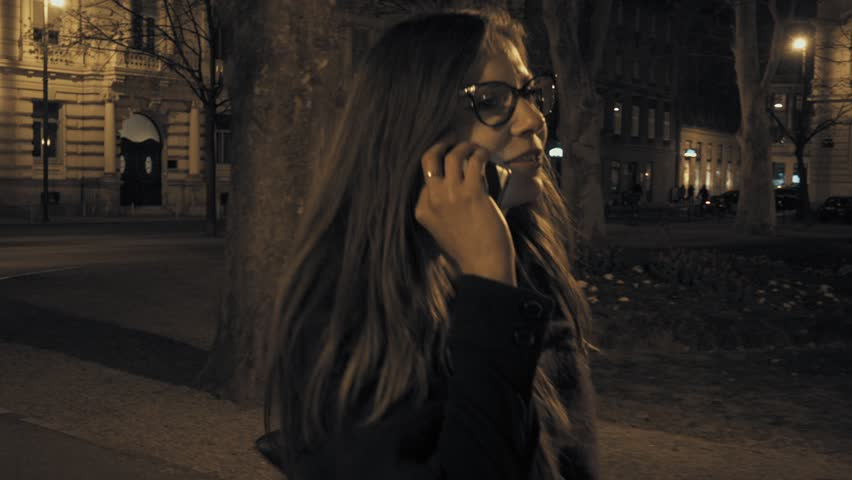 Young brunette woman in the city park typing and talking on the smartphone. Night time in the city.  | Shutterstock HD Video #25960928