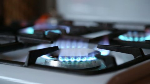 Natural gas inflammation in stove burner. Stove top burner turns on. Turns on gas stove burners. Blue gas. Stove top burner igniting into a blue cooking flame.
