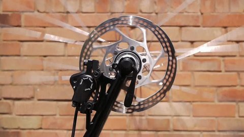 Spinning bicycle wheel against a brick wall in the background.