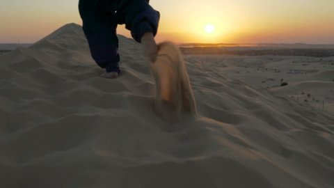 running up a hill sand dune in desert. running in sand dune in desert. two bare feet running in the sand
