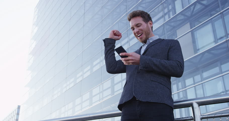 Business success and achievement - happy businessman cheering celebrating on cell phone. Young urban professional successful business man reaching personal goals. Smartphone app or video game concept. | Shutterstock HD Video #25989533