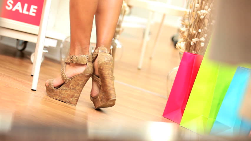 Young females admiring fashionable new shoes on sale in modern boutique legs only