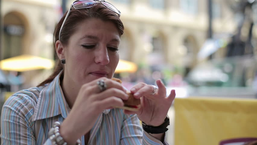 Woman eating sandwich, hamburger in bar