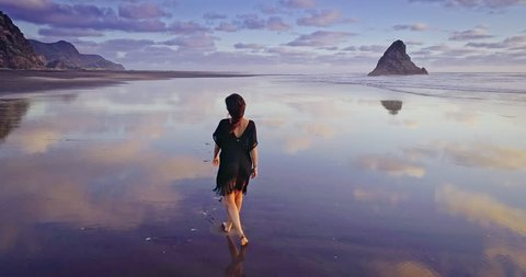 Aerial Of woman walking and running on a beach, karekare, Auckland, New Zealand