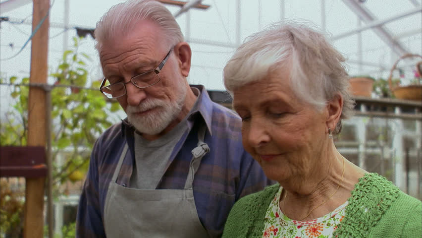 Elderly couple smelling a plant