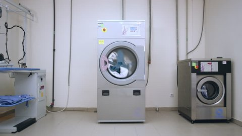 Industrial laundry room. Washer machines in laundry service. Industrial laundry machine washing clothes. Hotel laundry room. Industrial washer and dryer working