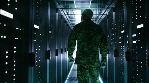 Soldier Walks into Data Center Through Sliding Doors and Walks along Rows of Working Rack Servers. Shot on RED EPIC-W 8K Helium Cinema Camera.