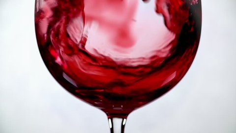 Filling wine glass with red wine super slow motion macro shot on white background.