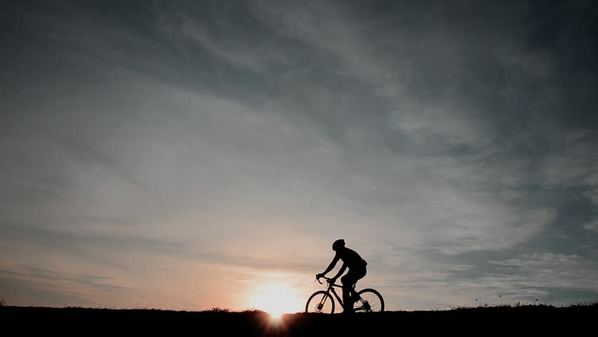 A man on a bike with a sunset #26016488